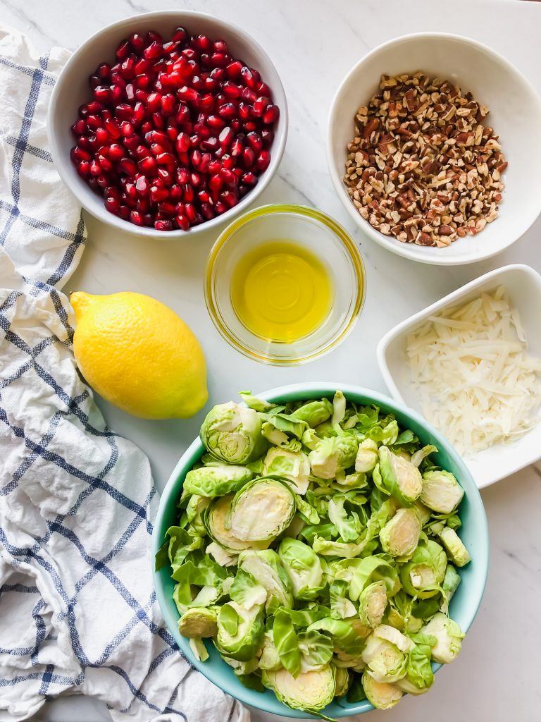bowls of brussels sprouts, lemon, olive oil, pomegranate seeds, pecans, parmesan cheese