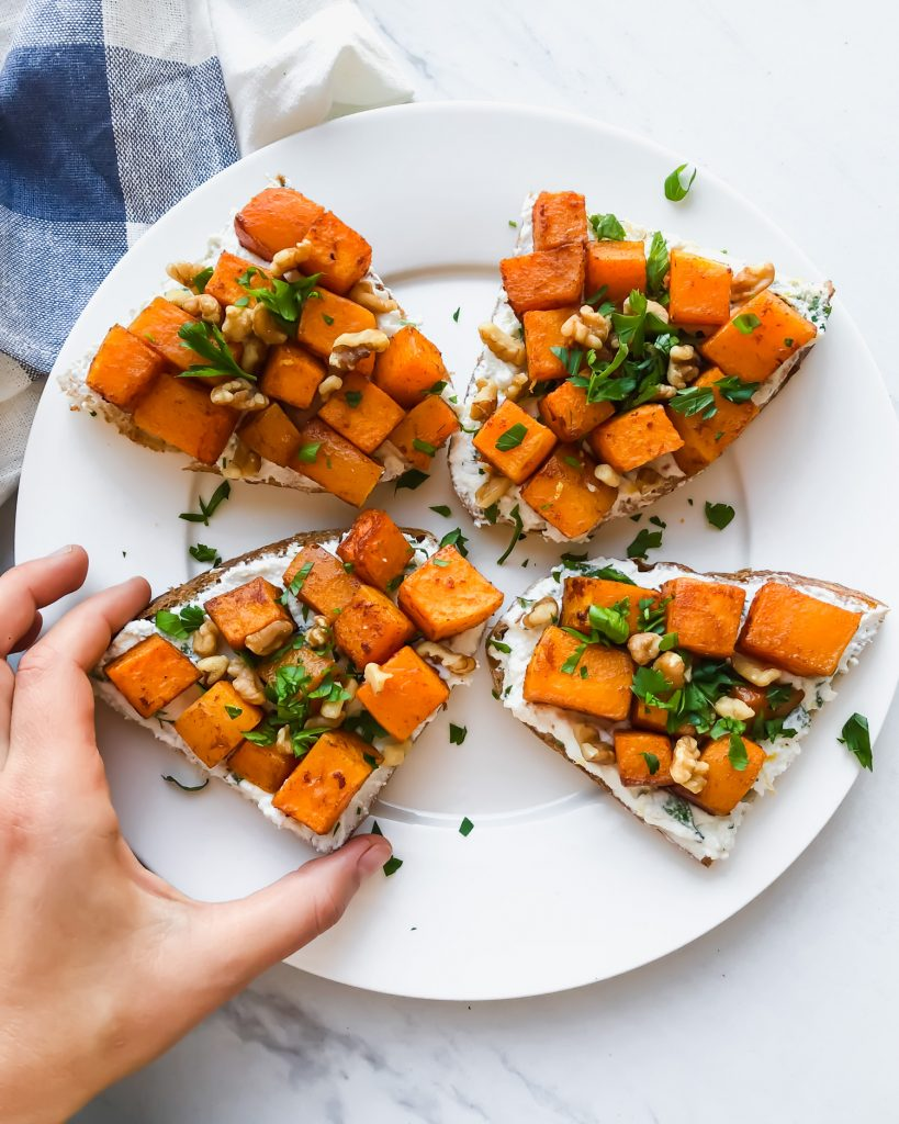 Lemon Ricotta Butternut Squash Toast on a plate with hand