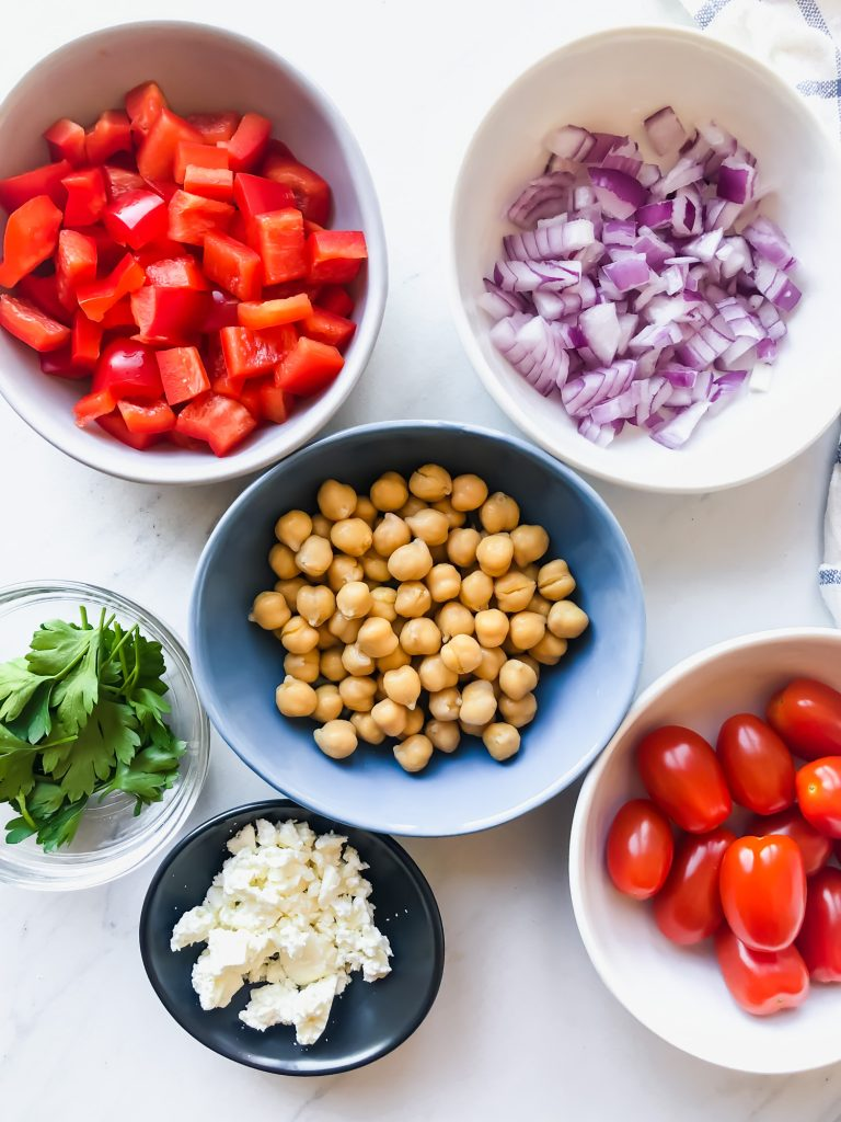 bowls of chickpeas, red bell peppers, cherry tomatoes, red onions, parsley, feta cheese