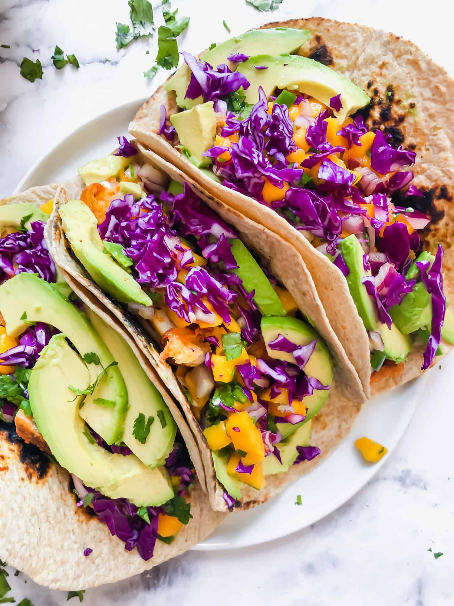 three fish tacos with mango salsa on a plate