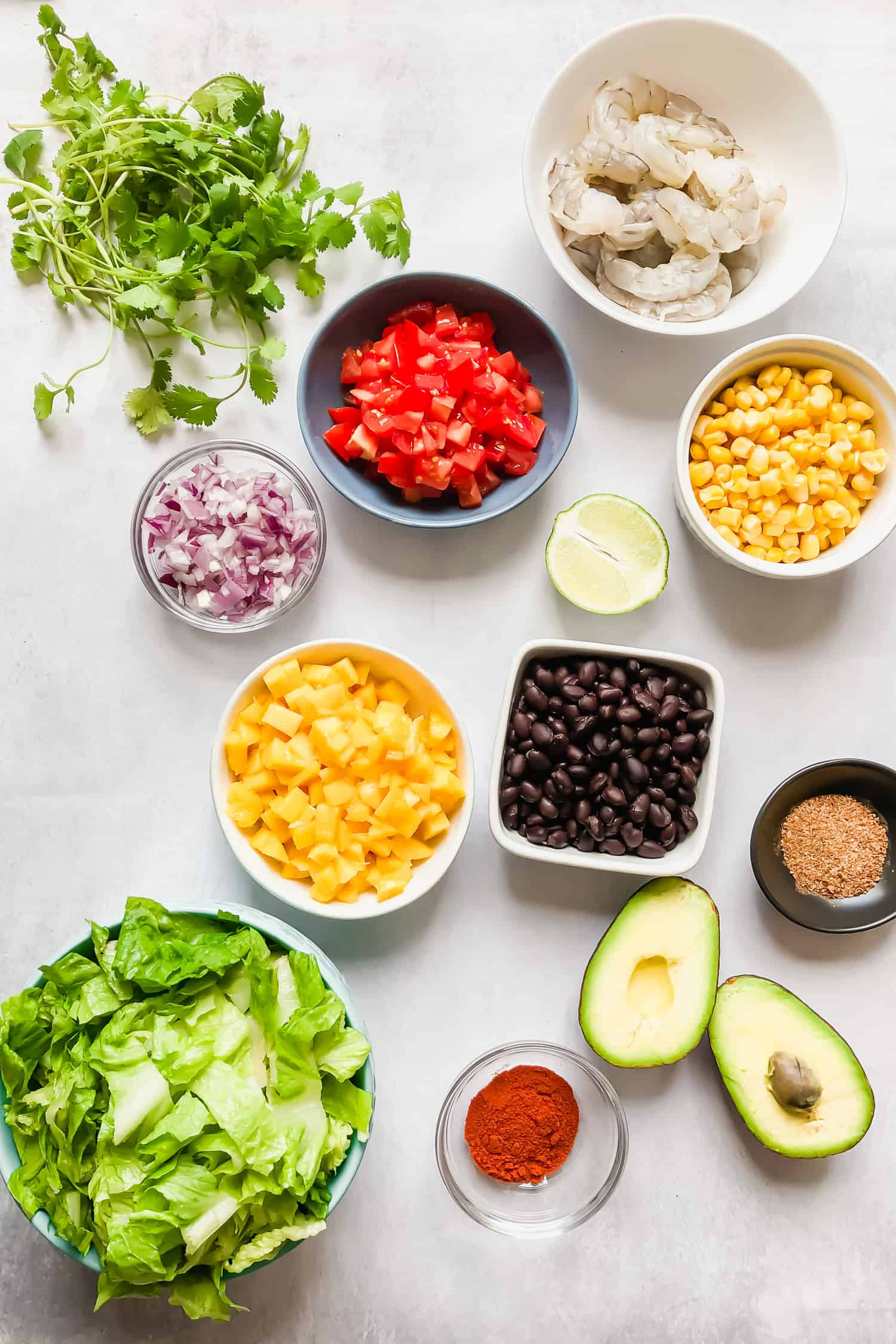 ingredients in bowls: lettuce, corn, beans, tomatoes, mango, shrimp, onion, lime, avocado, cilantro