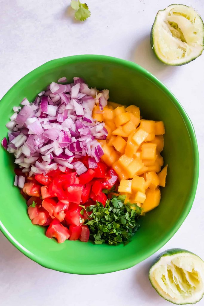 mango salsa ingredients in bowl: mango, tomato, cilantro, onion, lime