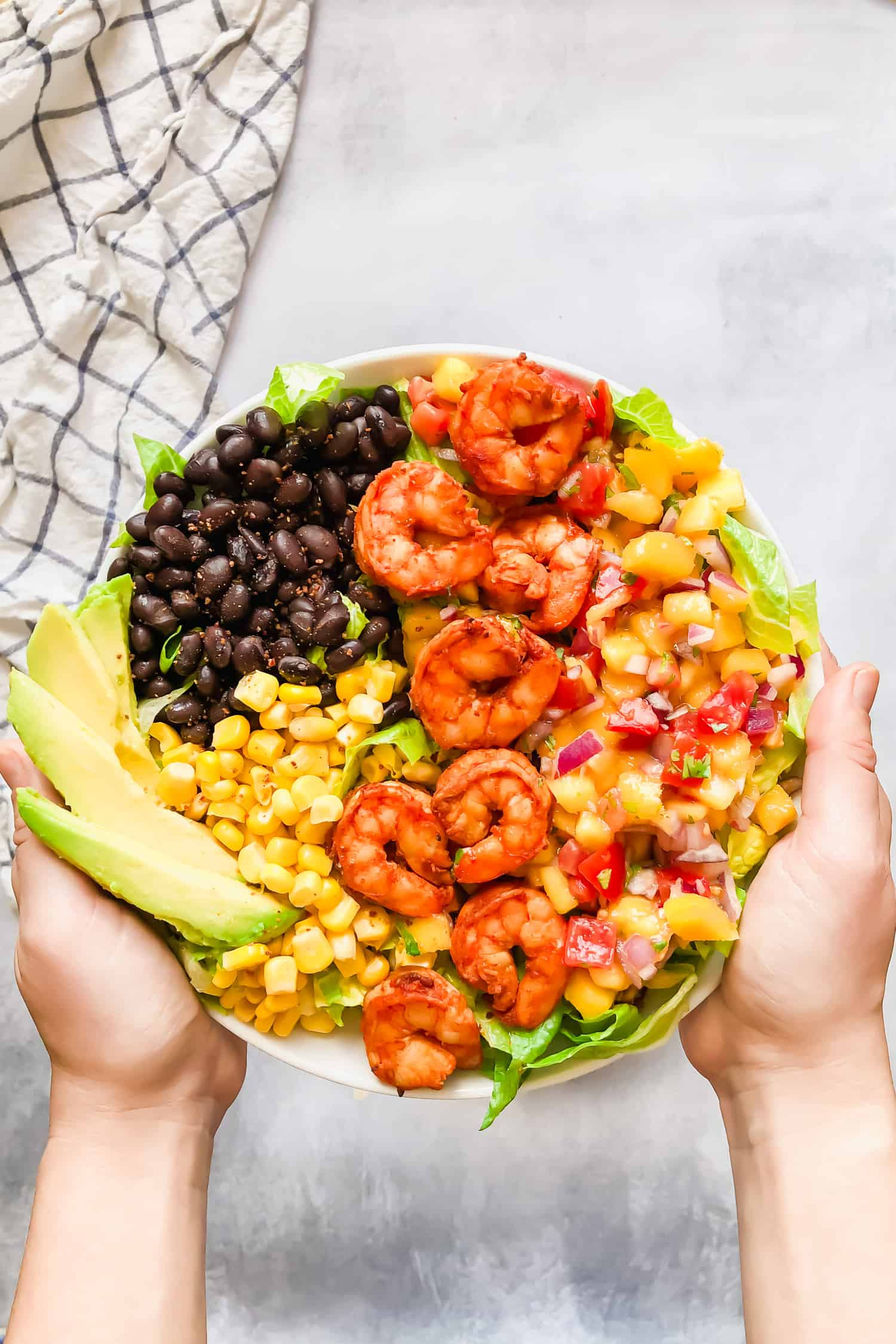 hands holding shrimp taco salad bowl