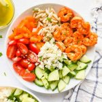 Mediterranean Shrimp Salad in a bowl with dressing on the side