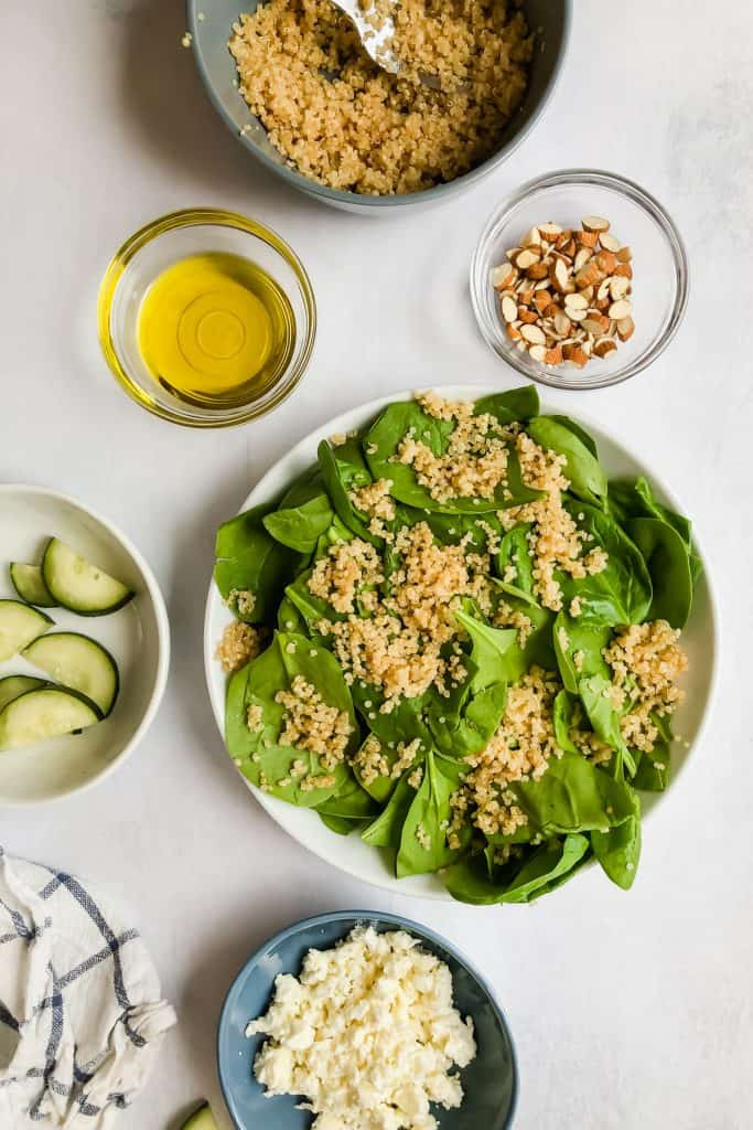 spinach and quinoa in a bowl surrounded by ingredients for Cucumber Strawberry Salad