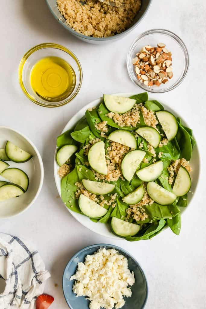 spinach, quinoa, and cucumbers in a bowl surrounded by ingredients for Cucumber Strawberry Salad