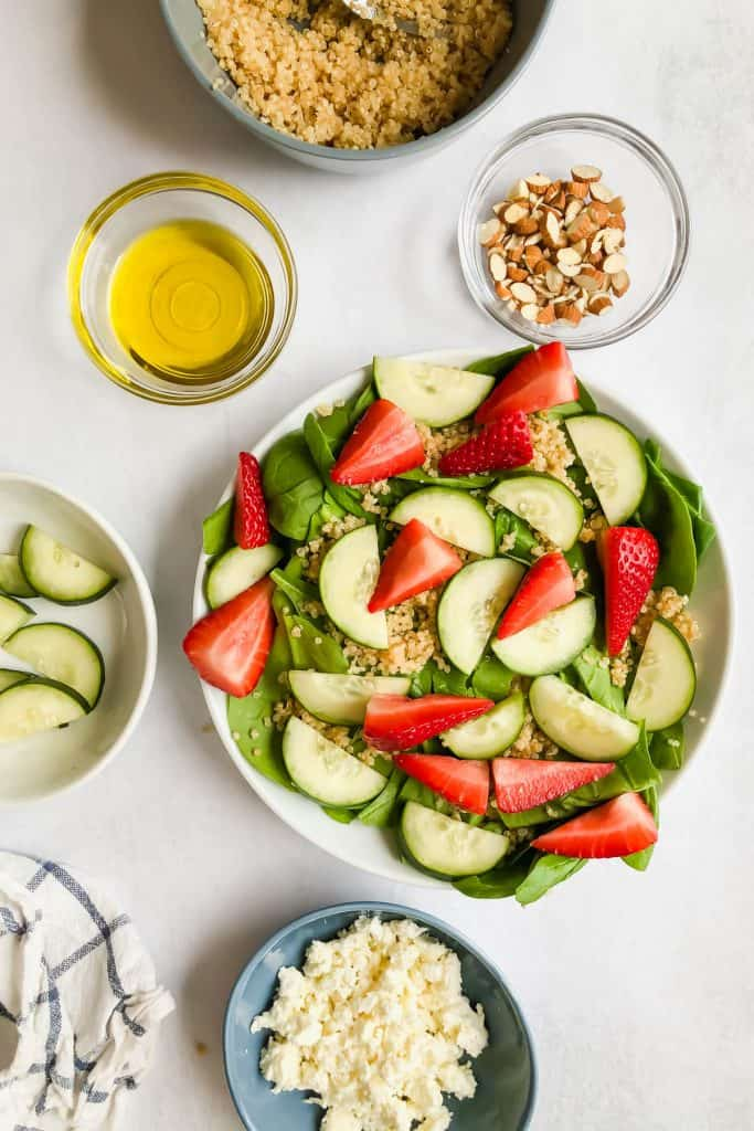 spinach, quinoa, strawberries, and cucumbers in a bowl surrounded by ingredients for Cucumber Strawberry Salad
