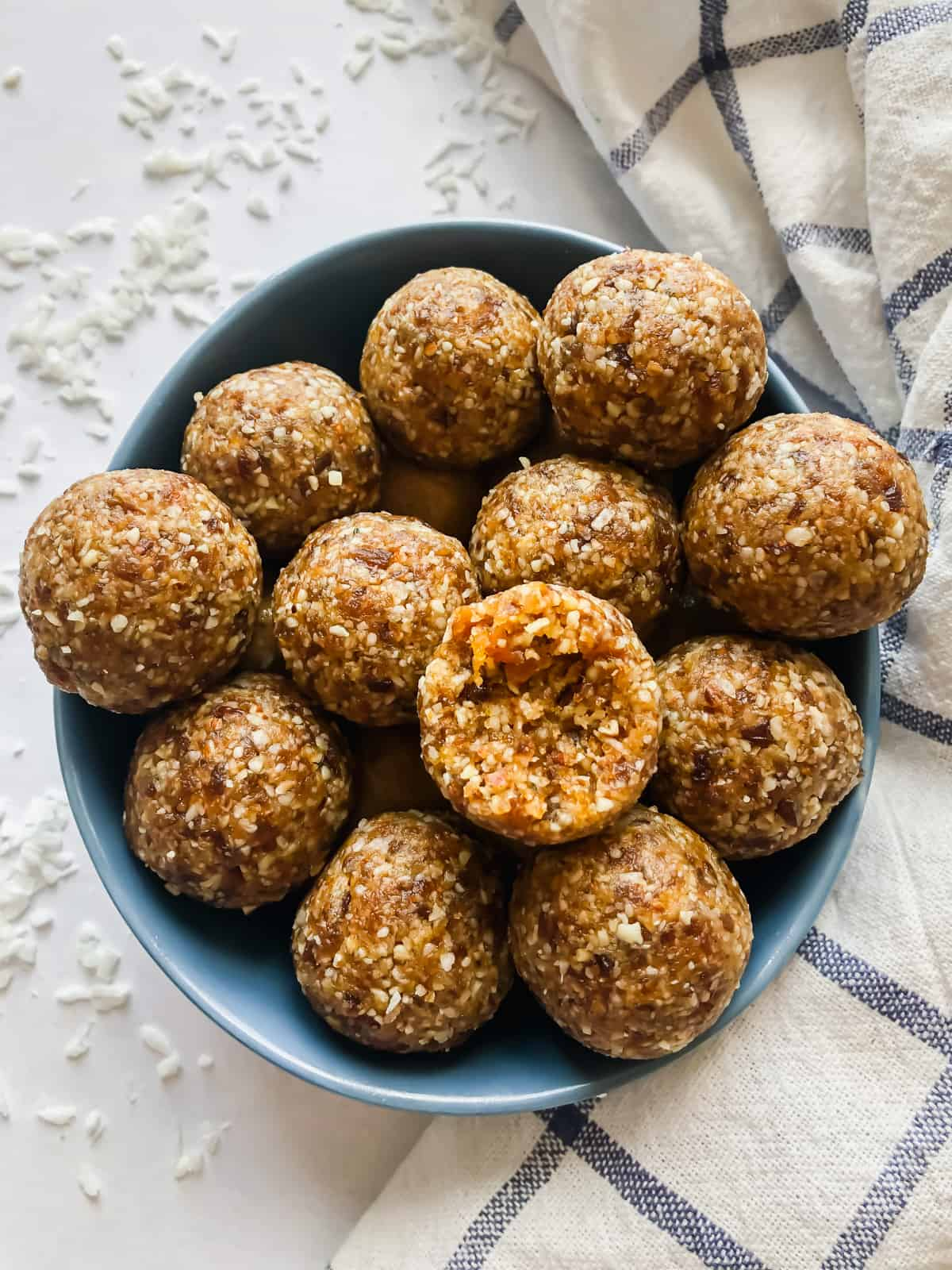 apricot bliss balls in a bowl surrounded by shredded coconut and a blue/white cloth napkin