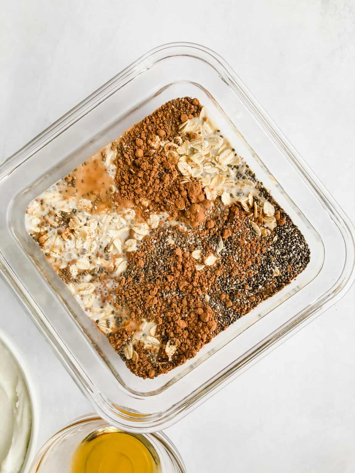 oats, cocoa, almond milk, chia seeds in a food storage container