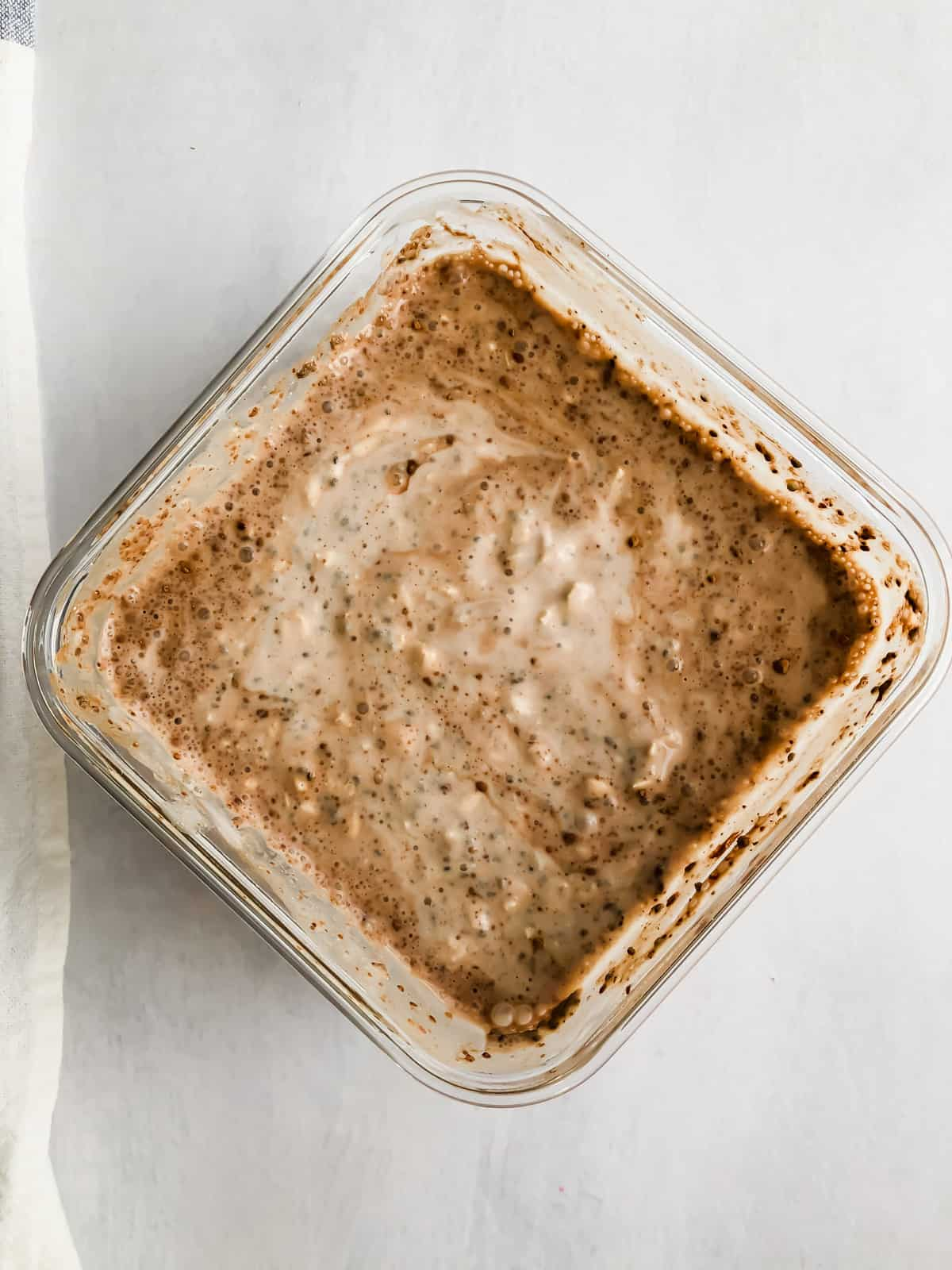 chocolate overnight oats stirred in a food storage container