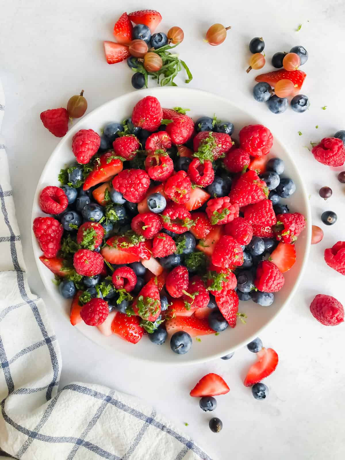 summer berry salad in a bowl surrounded by fresh summer berries