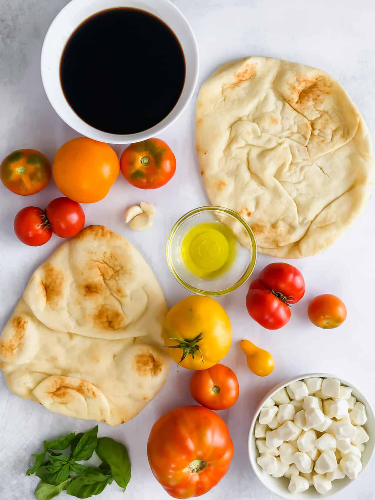 ingredients for caprese flatbread on white background