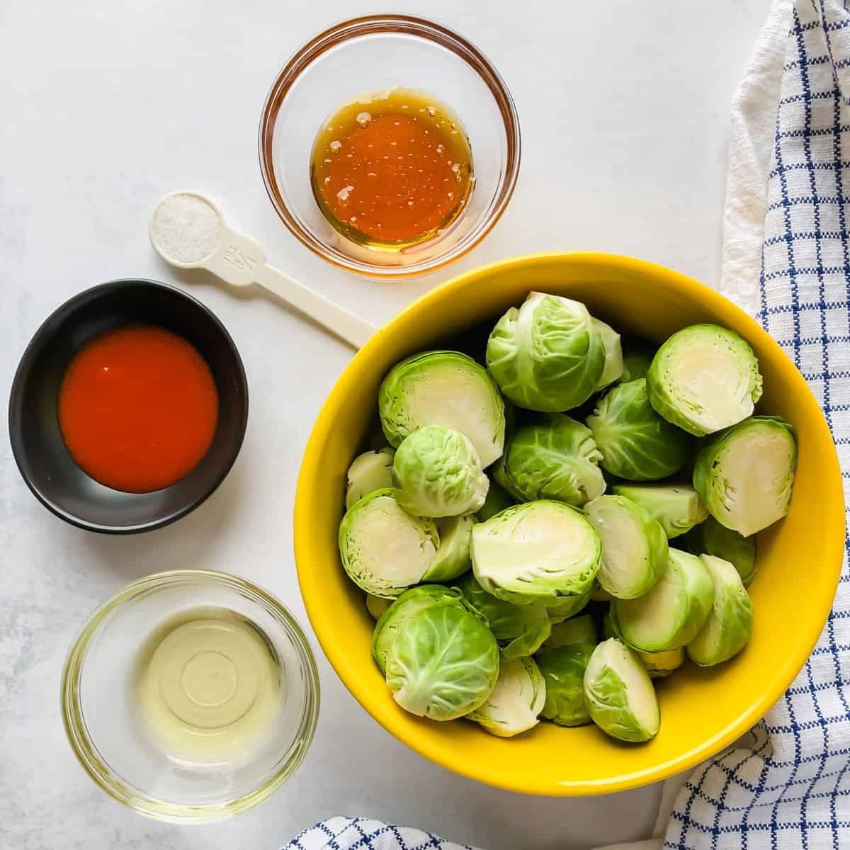 bowls filled with brussels sprouts, sriracha, honey, oil, and salt on a white background