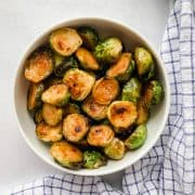 roasted brussels sprouts in a white bowl with a blue napkin