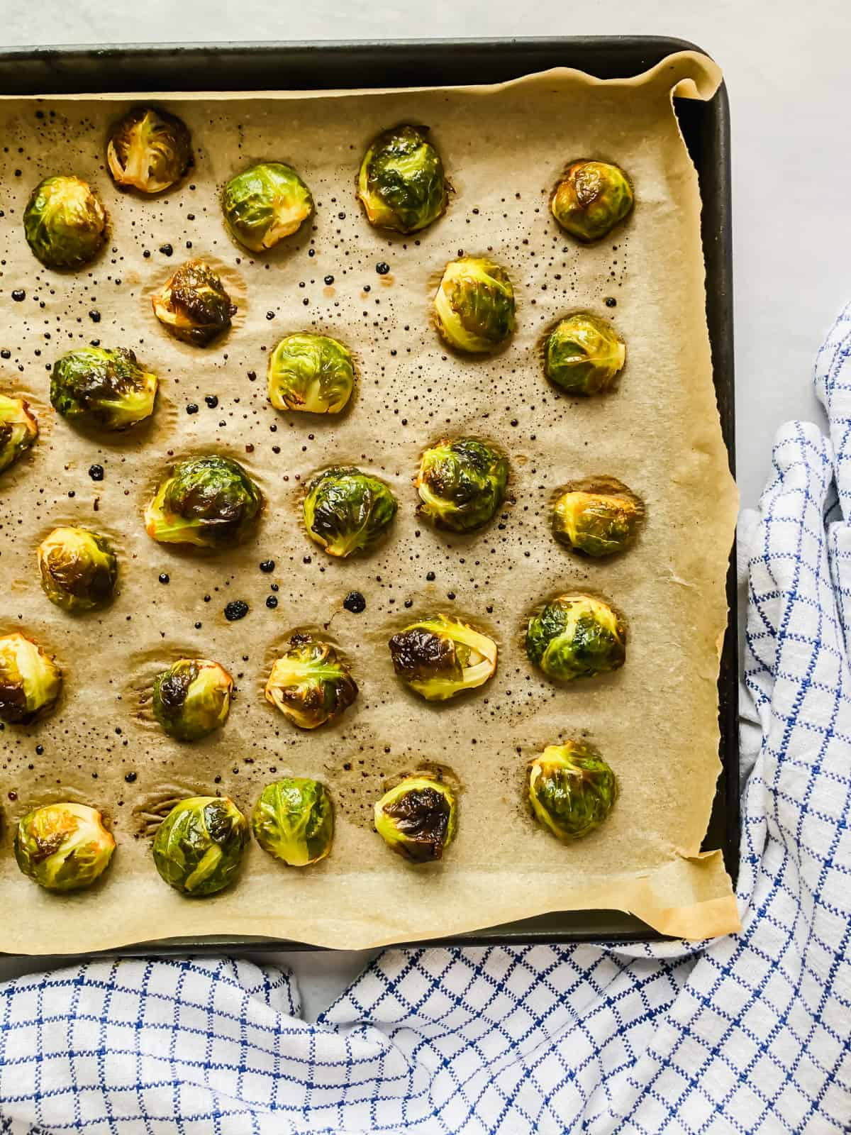 roasted brussels sprouts on a parchment-covered baking sheet on a white background