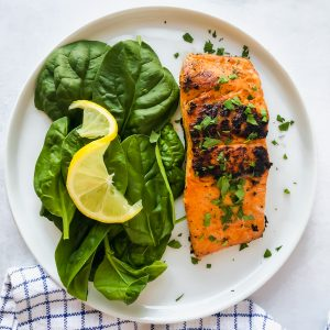 Paprika salmon spinach on a white plate on a white surface with a blue napkin