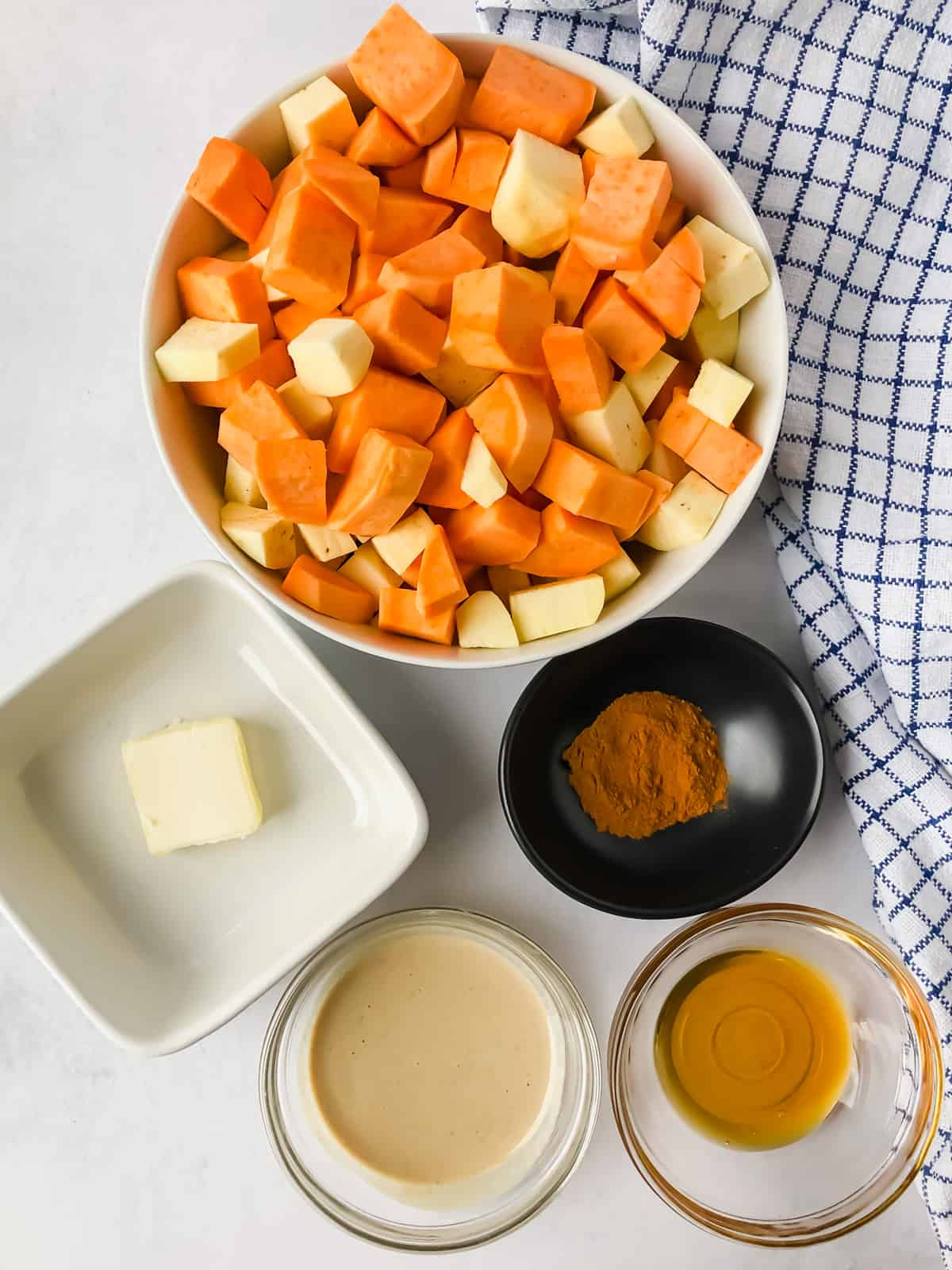 sweet potatoes, butter, cinnamon, tahini, maple syrup in bowls on white surface with blue napkin