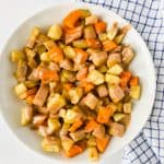sauteed sweet potatoes drizzled with tahini butter in bowl on white surface with blue napkin