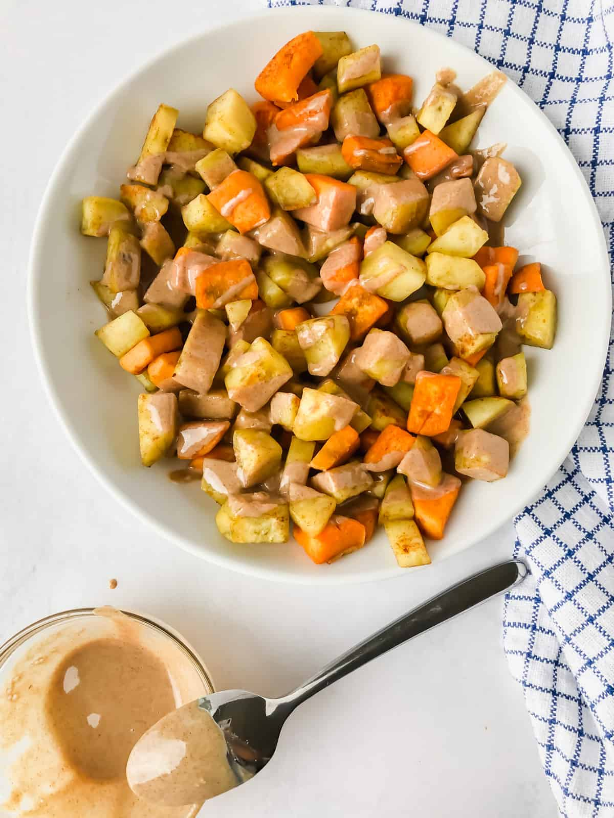 sauteed sweet potatoes and tahini butter in bowls on white surface with blue napkin