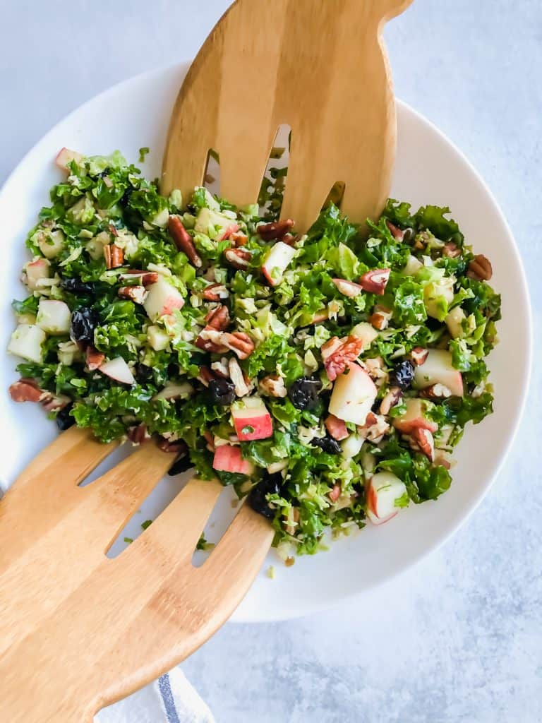 kale brussels sprout salad in bowls on white surface