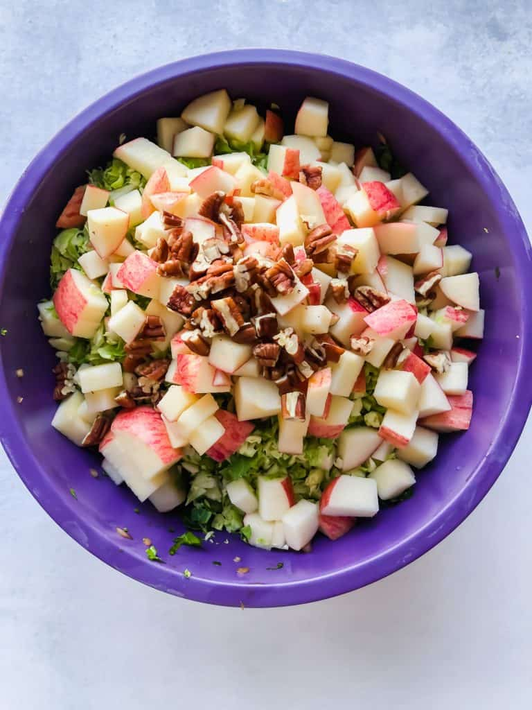 chopped kale, brussels sprouts, apples, and pecans in purple bowl
