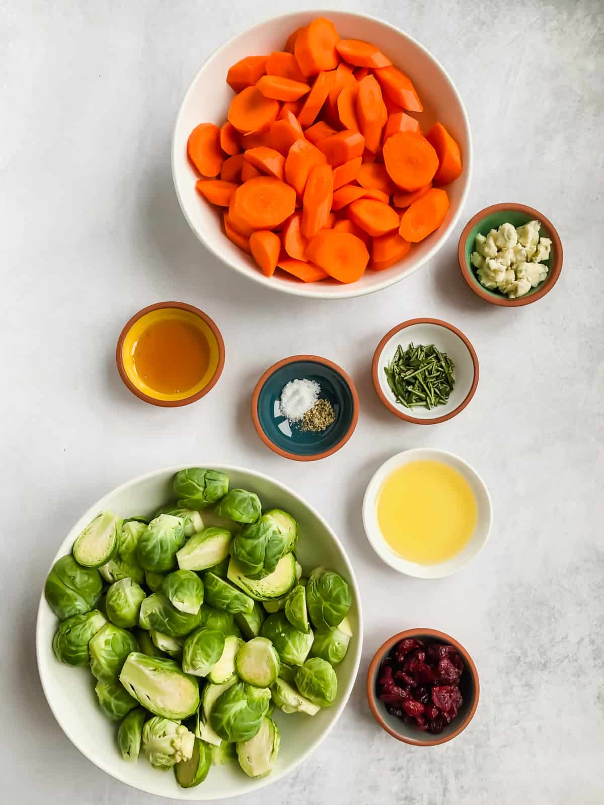 ingredients in bowls on white surface: carrots, brussels sprouts, honey, salt, pepper, oil, herbs, cranberries, cheese