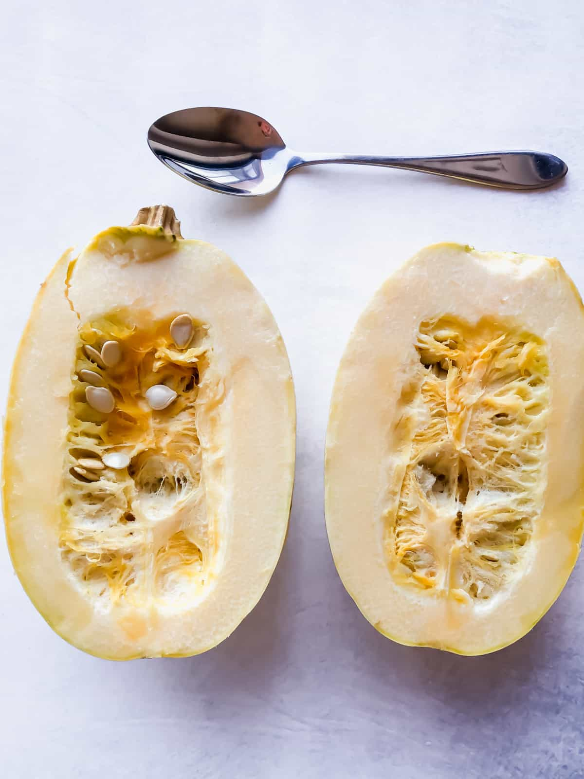 spaghetti squash halves with a spoon on a grey surface