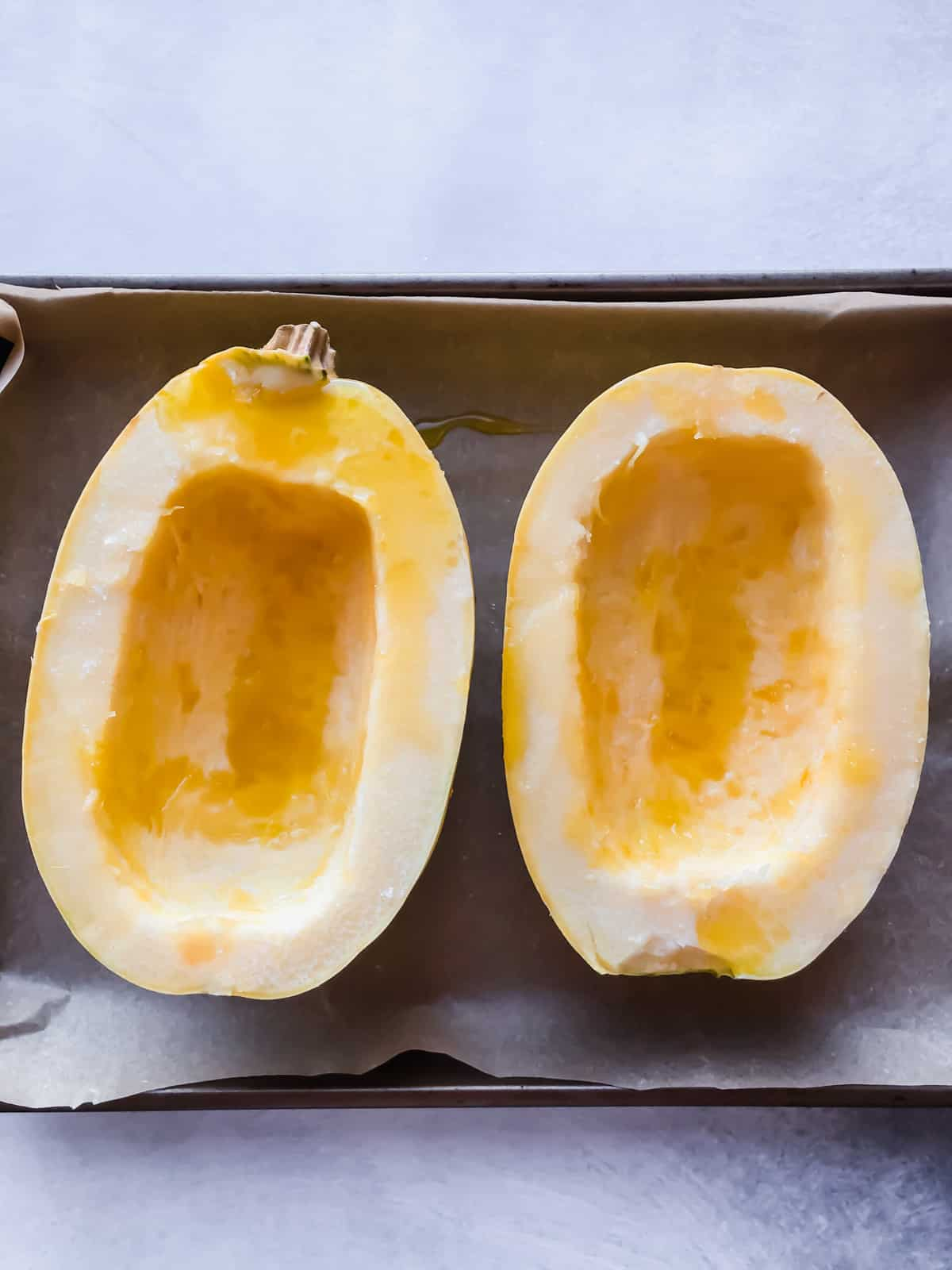 spaghetti squash halves on parchment paper on a grey surface