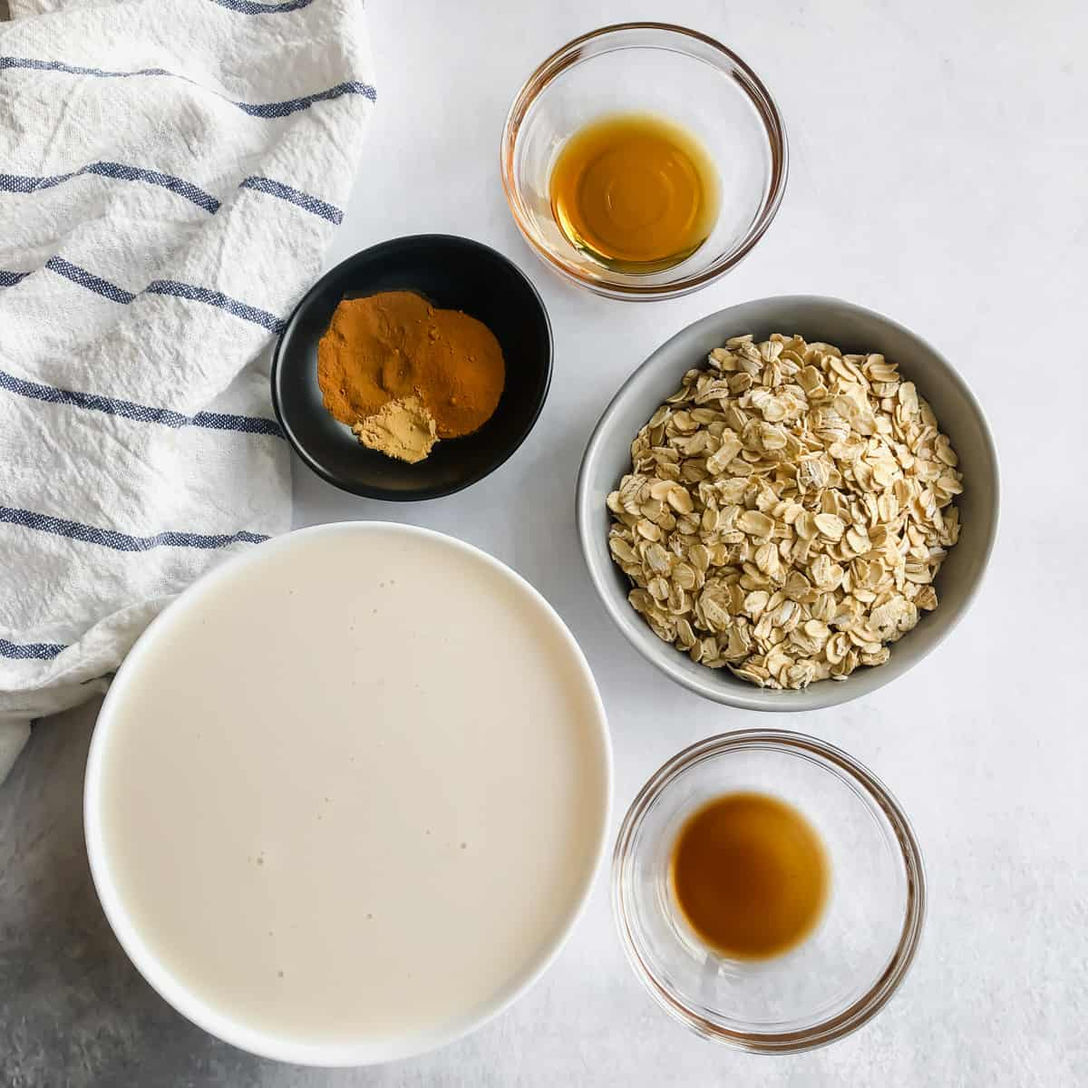 Bowls filled with turmeric, cinnamon, ginger, oats, vanilla extract, maple syrup, and almond milk on white surface with blue-and-white napkin