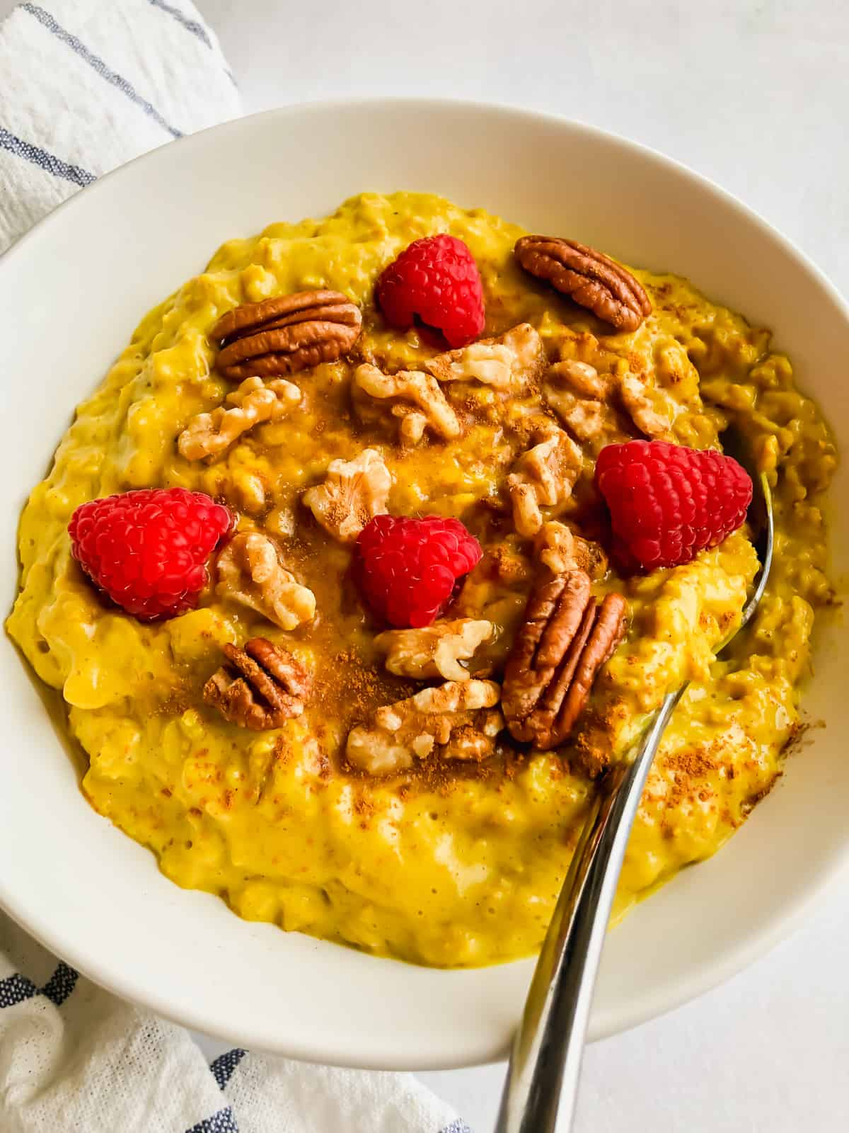 turmeric oatmeal topped with fruit and nuts in a white bowl on white surface