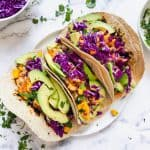 three fish tacos with mango salsa and avocado on a white plate and white background